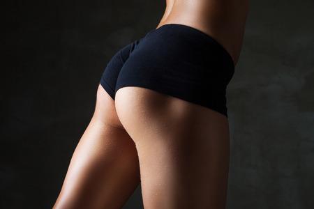 Beautiful fit, sexy female body on dark grey background photo