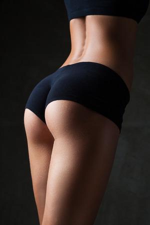 Mooie fit, sexy vrouwelijk lichaam op donkere grijze achtergrond Stockfoto