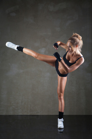 Beautiful girl kicking with the leg on dark grey background