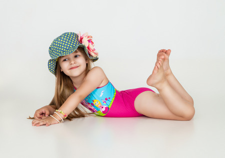 swimming costumes: little girls posing in swimsuits and hat in studio. Fashion shot Stock Photo