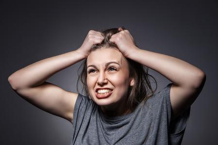 Angry woman screaming over dark grey background Standard-Bild
