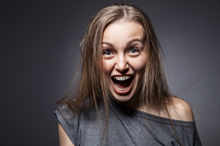 Angry woman screaming over dark grey background Stock Photo
