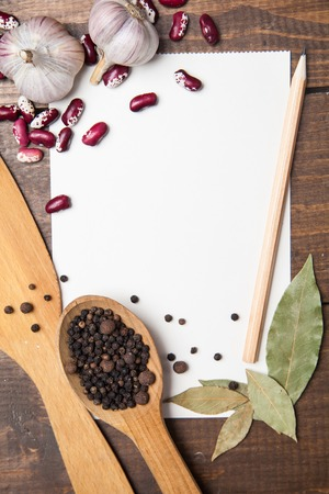 paper for recipes, pepper and spices on wooden table photo