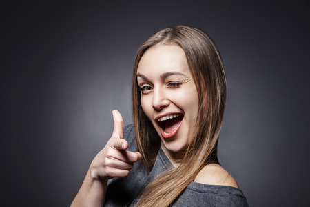 sticking to: Young Happy Woman Sticking Out Her Tongue Over a Grey Background Stock Photo