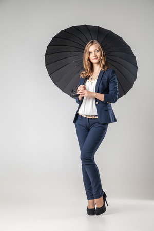 woman umbrella: Beautiful sexy young business woman with evening make-up dressed in pants and suit business clothes for meetings and walks and umbrella