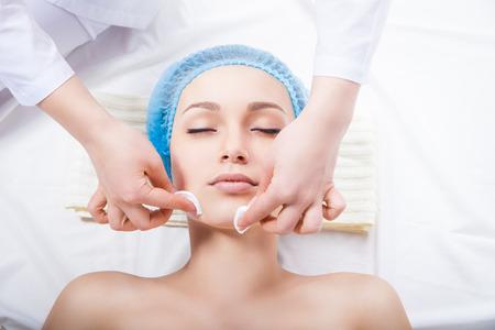piel humana: Cuidado de la piel - mujer de limpieza de la cara por esteticista sobre fondo blanco