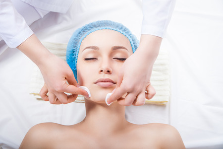 traitement: Soins de la peau - femme de ménage visage en esthéticienne sur fond blanc Banque d'images