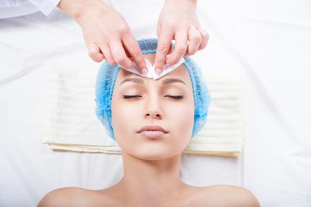 tratamientos faciales: Cuidado de la piel - mujer de limpieza de la cara por esteticista sobre fondo blanco