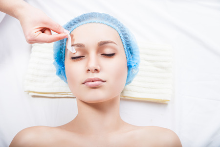 tweezing eyebrow: young woman remove hair from her eyebrows in spa salon