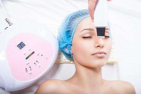 woman getting ultrasound skin cleaning at beauty salon photo