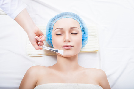 pulizia viso: Ragazza con un estetista presso il salone spa. Estetista esegue procedure cosmetiche. L'applicazione di crema cosmetica a pennello