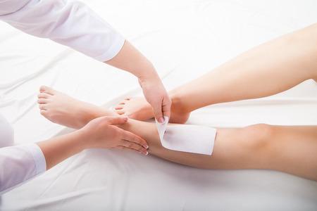 depilacion con cera: Esteticista depilación las piernas de la mujer en un salón de spa  Foto de archivo
