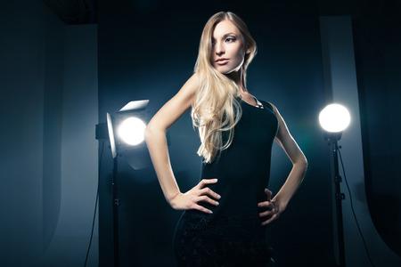 Mooie vrouwelijke model stellen bij studio in het licht knippert