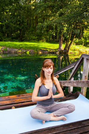 Young girl doing yoga lotus pose in the park photo