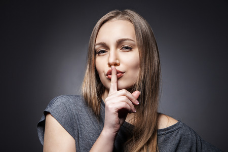 shushing: Young Woman Gesturing for Quiet or Shushing over dark grey background