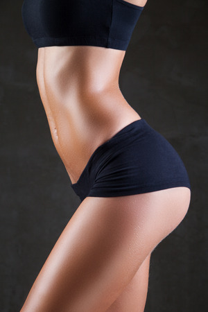 Slim tanned womans body over dark gray background