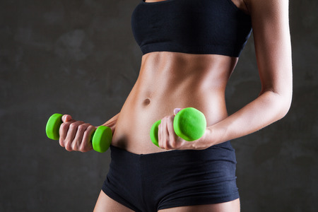 Body of young fit woman lifting dumbbells over dark grey background
