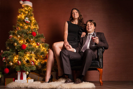 Christmas Couple. Happy Smiling Family at home celebrating New Year photo