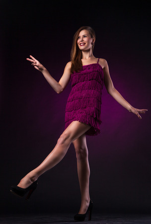 Beautiful sexy young woman in purple dress dancing on dark purple background in studio - series of photos Stock Photo