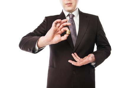 miser: businessman holding coins in his hand isolated over white
