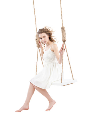 barefooted: Beautiful bare-footed woman sitting on swing  isolated on white background Stock Photo