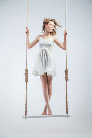 girl on swing: Young bare-footed girl on swing looking looking left. Isolated over the white background. Stock Photo