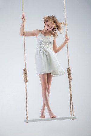 barefooted: Young bare-footed girl on swing looking looking down. Isolated over the white background.