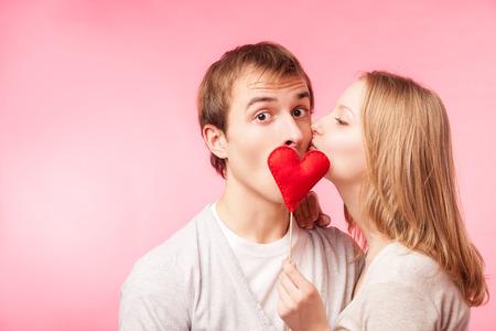 jovenes enamorados: Chica joven que se besa del ni�o escondido detr�s de un peque�o coraz�n rojo. Aislado sobre fondo rosa. Foto de archivo