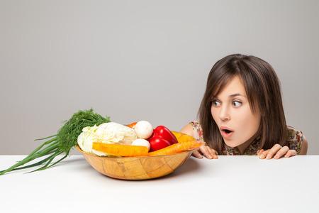 woman looking at green vegan food. surprise emotion.