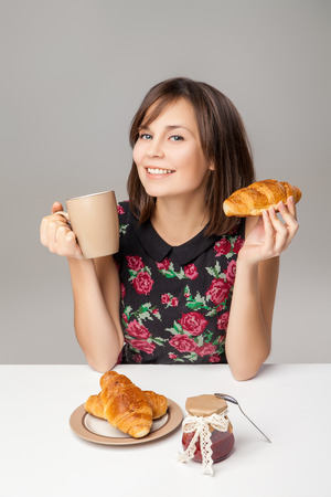 Healthy Young Woman With Breakfast Croissants and Cup Stock Photo