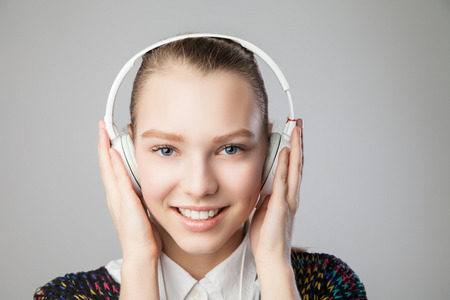 Closeup of smiling woman with headphones listening music on player. Music teenager girl portrait against isolated grey background photo