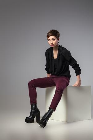 jambes �cart�es: belle femme brune mince assis les jambes �cart�es sur cube sur fond gris