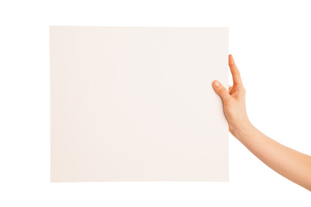 one hand holding a big white piece of cardboard. Hand points left. photo