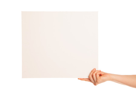 in hand a big blank sheet of white paper shown up.  Hand holds edge. Isolated, over white background. photo