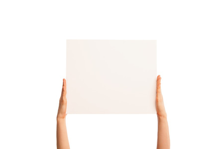 Isolated hands holding a piece of paper up, fingers straight. Over white background. photo