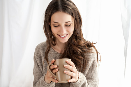 mooie vrouw genieten van koffie in de ochtend zitten bij het raam Stockfoto