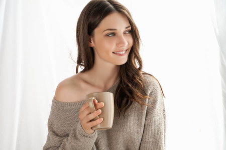Closeup of beautiful girl with cup enjoying the freshness of the new day and looking through the window.