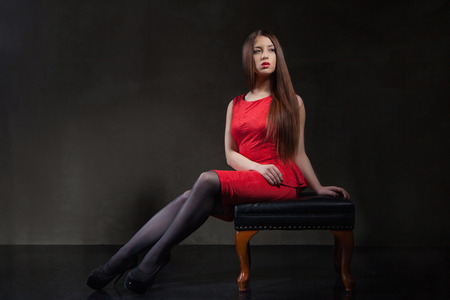 A beautiful model girl   sitting on a  chair in studio wearing a short red dress, black tights  and black high heels shoes with long hair and beautiful make-up p.