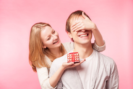 Woman surprising a man with present over pink background. Isolated.