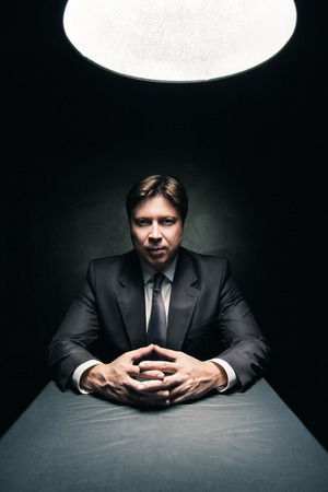 Man in suit sitting in dark room illuminated only by light from a lamp and looking in camera photo