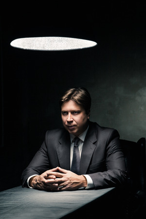 Side view of man in suit sitting in dark room illuminated only by light from a lamp