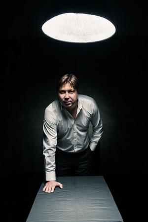 Man in donkere kamer alleen verlicht door het licht van een lamp en kijken in de camera, met de hand op tafel Stockfoto