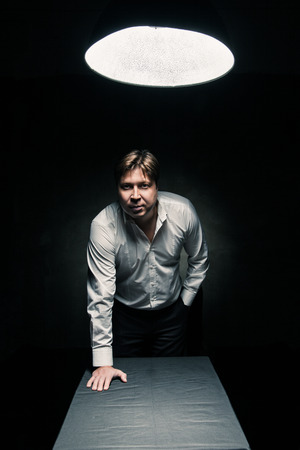 Man standing in dark room illuminated only by light from a lamp and looking in camera, hand on table