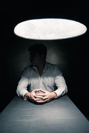 nerveux: Man dans une pi�ce sombre �clair�e seulement par une lumi�re provenant d'une lampe sans visage vu
