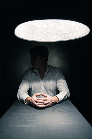 Man in a dark room illuminated only by a light coming from a lamp no face seen Stockfoto