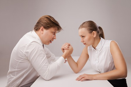 male female: Man and woman in arm wrestling gesture on working table during meeting. Isolated over grey background.