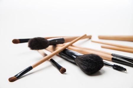 mujer maquillandose: Conjunto de cepillos cosm�ticos. Cepillos del maquillaje sobre un fondo blanco