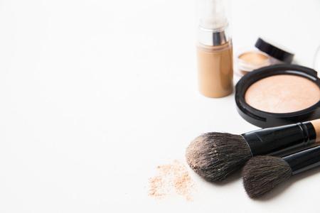 Powder, foundation and brushes isolated on the white background photo