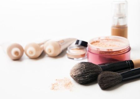 Powder can ,  tubes of foundation in a row and brushes isolated on the white background photo