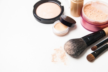 Powder, foundation and brushes isolated on the white background